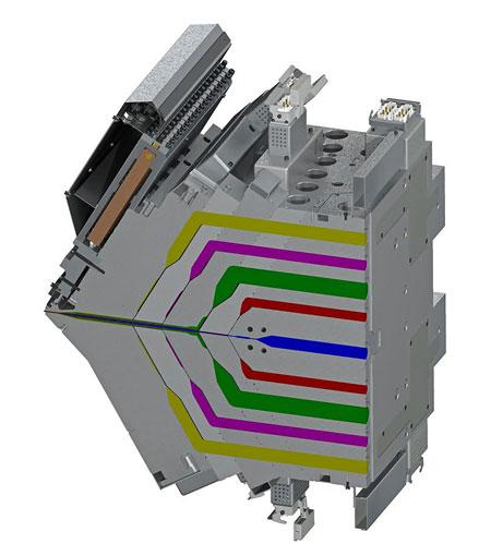 Representação do corte vertical da matriz de 9 manifolds da Nordson EDI, com fluxos de polímero apresentados em diferentes cores. Os fluxos combinados formam uma estrutura única de camadas múltiplas que sai da matriz à esquerda. Na parte superior esquerda, pode-se ver a unidade de ajuste automático de lábios.